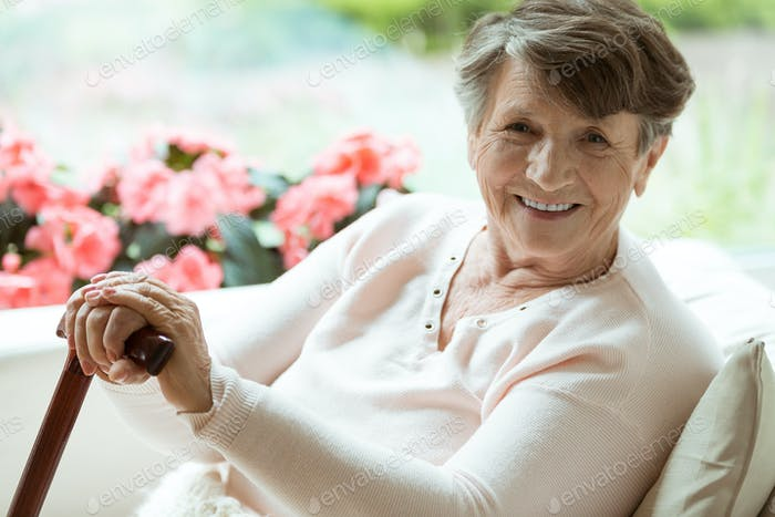 Woman with walking stick smiling