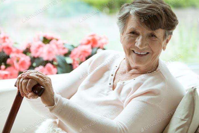 Mujer con bastón sonriendo