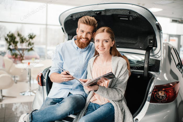 Happy couple with catalog sitting on car trunk in dealership salon