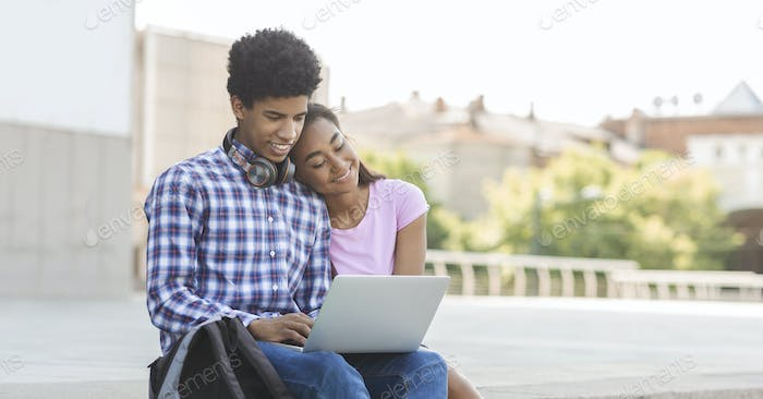 Couple of teenagers in love using laptop outdoors together