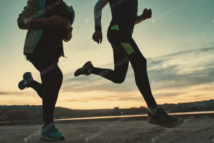 Sportive people legs running at sunrise