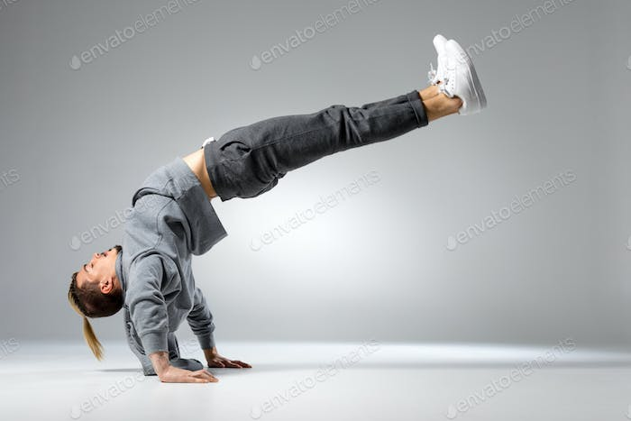 Young handsome concentrated man performing dance movement