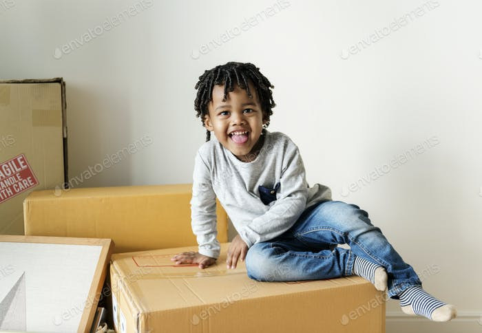Young cheerful black boy moving to new house