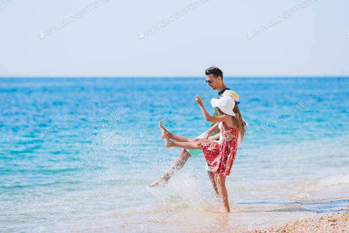 Adorable kids and their dad at beach during summer vacation