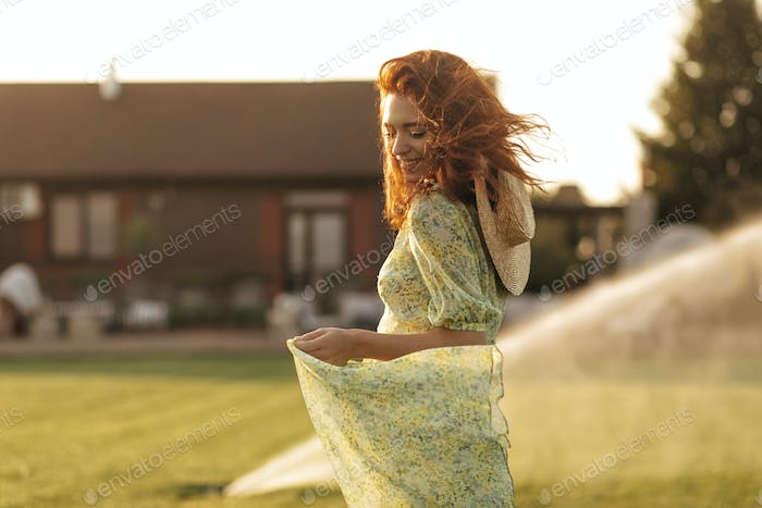 Red haired fashionable young lady straw modern hat in trendy green and yellow dress smiling with cl