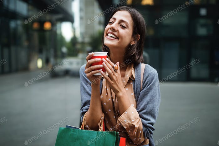 Happy young woman drinking take away coffee and walking with bags after shopping in city