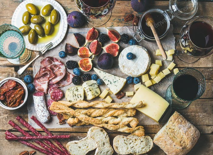Wine, snack set with meat, bread, olives, sun-dried tomatoes, berries
