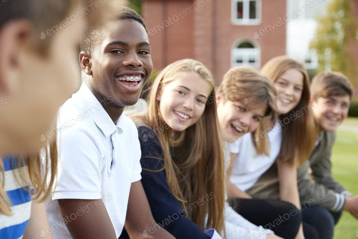 Thumbnail for Group Of Teenage Students Sitting Outside School Buildings
