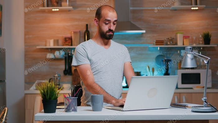 Exhausted man yawning sitting in kitchen at laptop