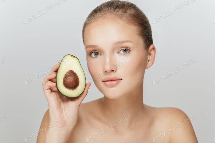 Portrait of young attractive woman without makeup holding half o