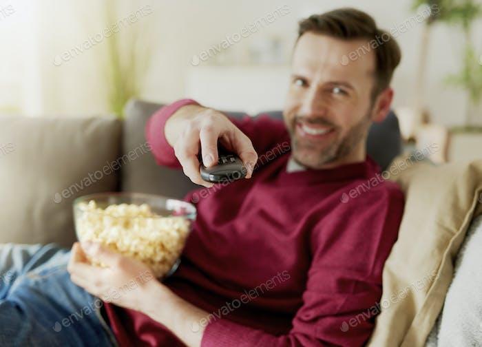 Cheerful man watching TV at home