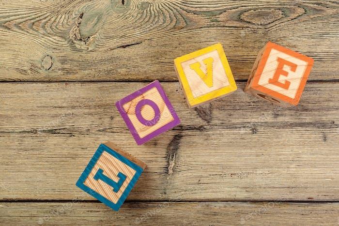 Palabra amor de bloques de madera de los niños sobre fondo de madera