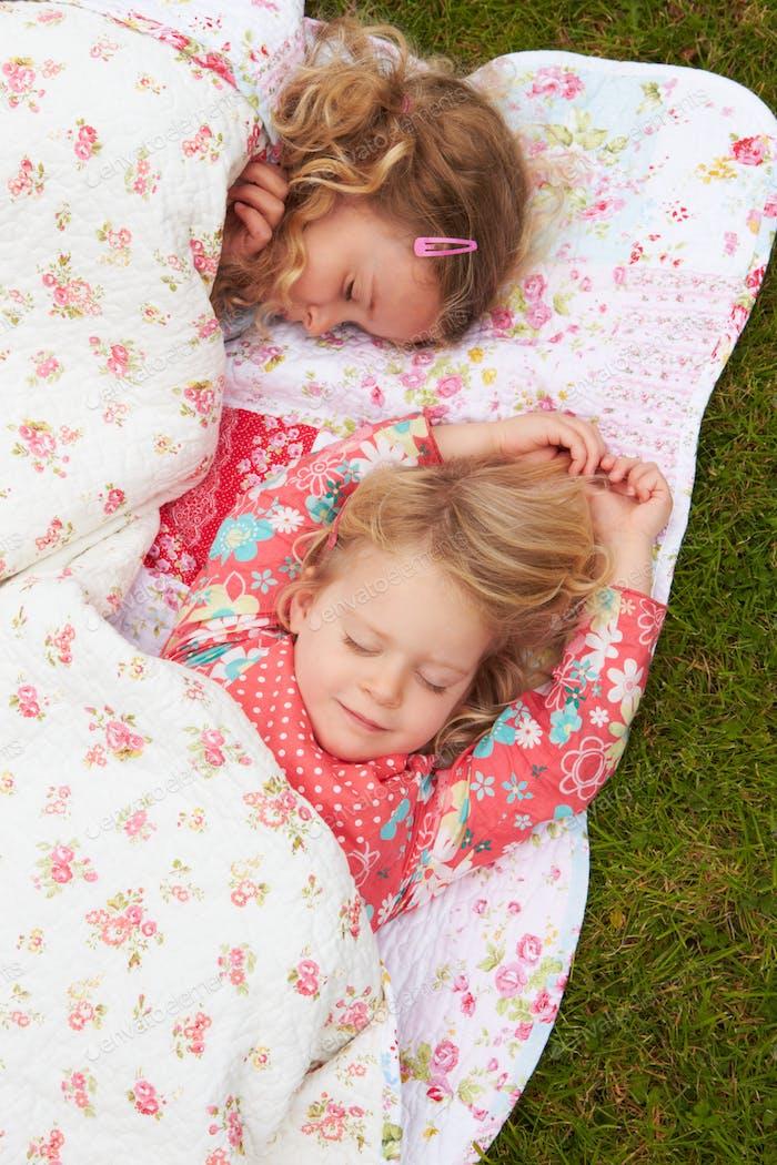 Dos niñas tumbado debajo de la manta en camping vacaciones