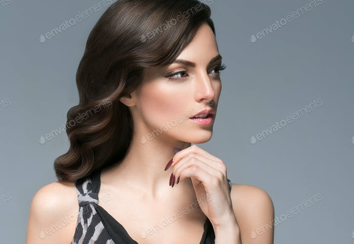 Beautiful woman with curly hairstyle portrait over gray background. Female young beauty model
