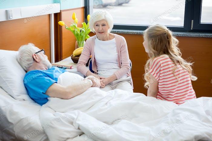 Großmutter und Enkelin besuchen Patienten im Krankenhaus. Männlicher Patient im Krankenhausbett Konzept