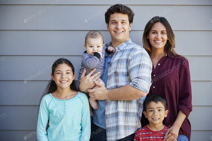 Portrait Of Happy Family With Baby Standing Outside Grey Clapboard House