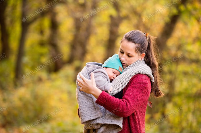Young mother with baby son on a walk in autumn forest.