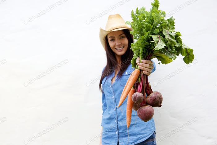 Smiling woman showing carrots and beets