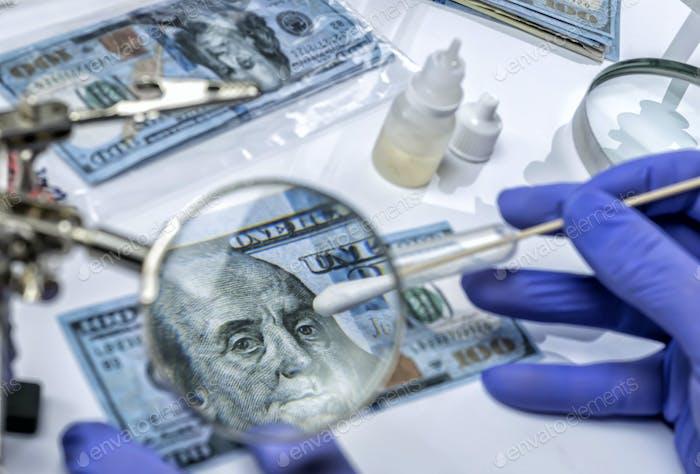 Police scientist investigates fake dollar bills and passports