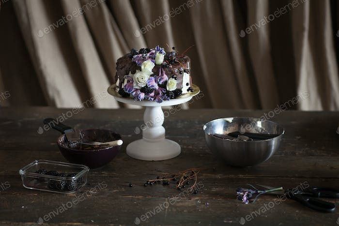 chocolate cake with flowers in dark interior