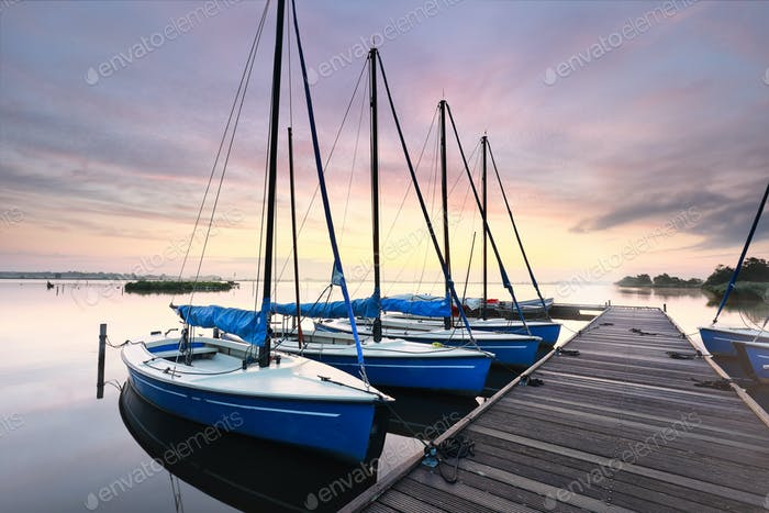 few yachts by pier at dawn