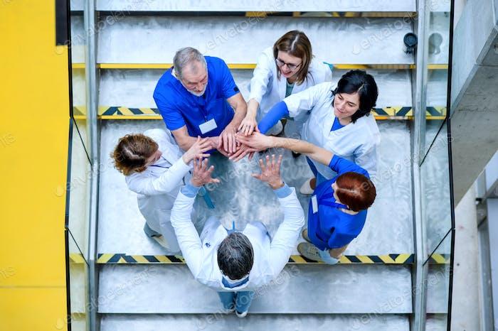 Draufsicht der Gruppe von Ärzten, die auf Treppen stehen und die Hände zusammensetzen