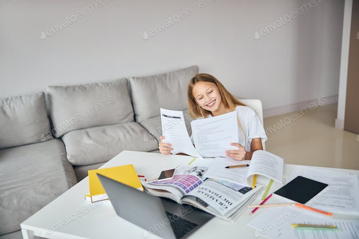 Joyful adolescent girl is comparing two worksheets
