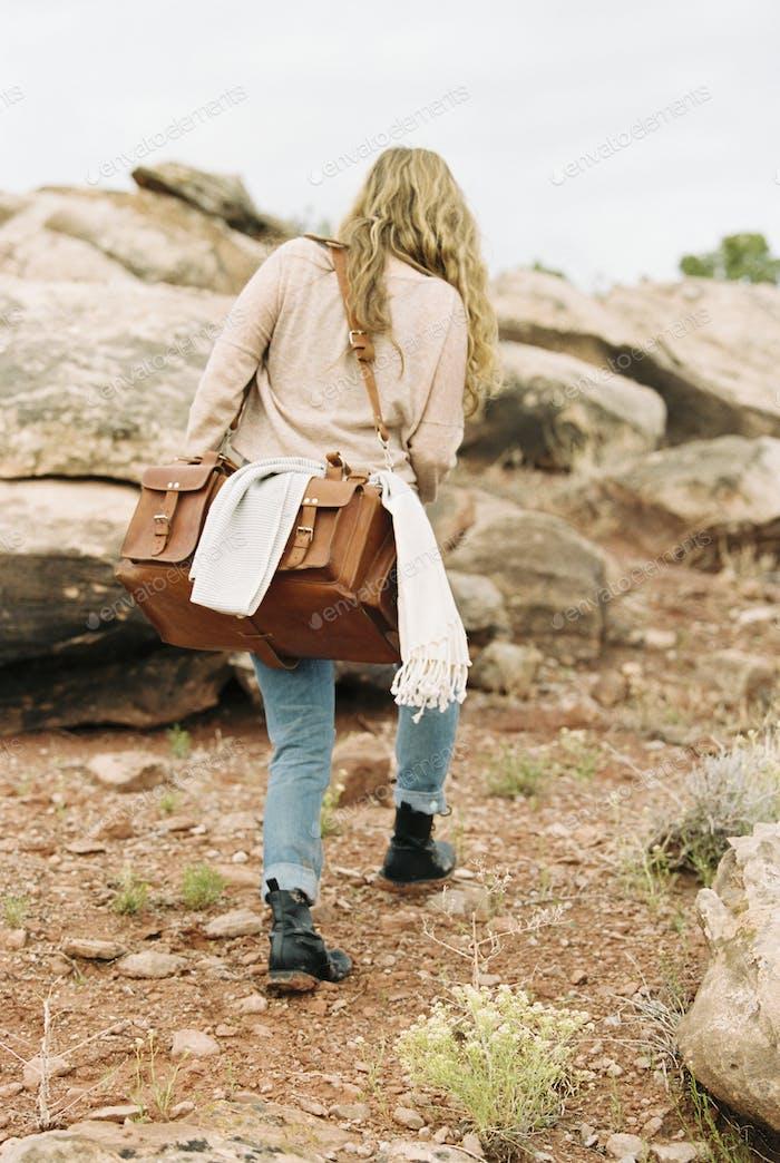Woman walking across rocks in a desert, carrying a leather bag.