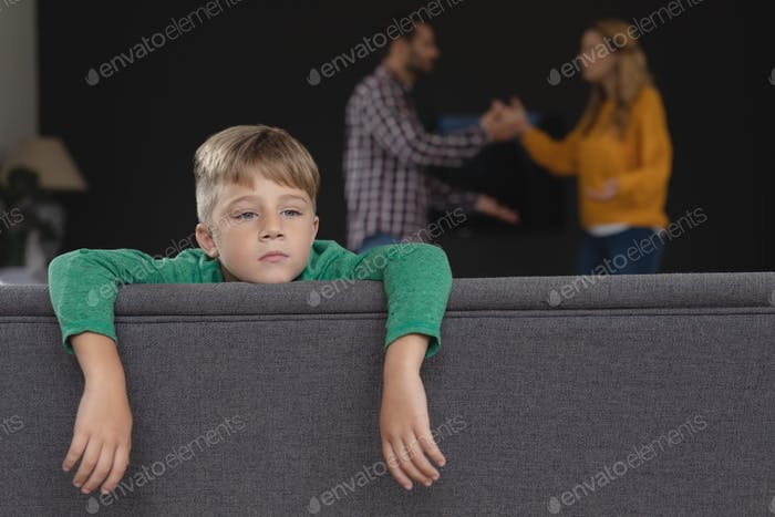 Sad boy leaning on sofa while Caucasian parents arguing in background