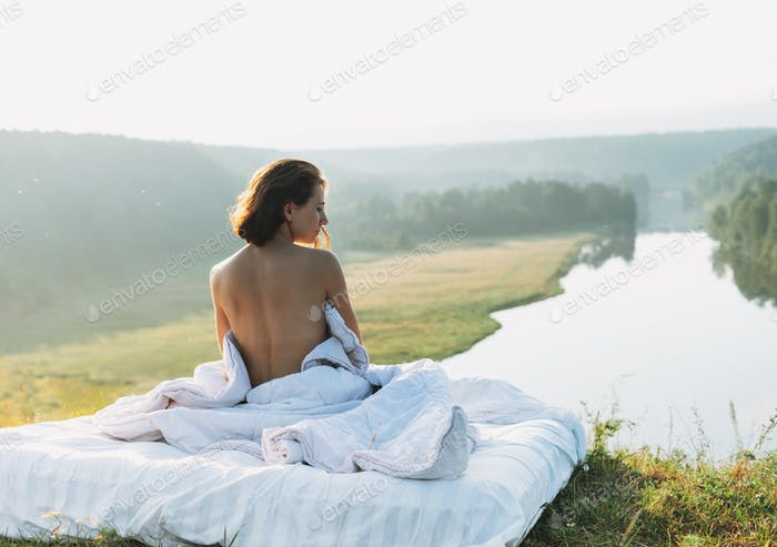 Young woman sitting in bed with white bed linen in nature against beautiful landscape