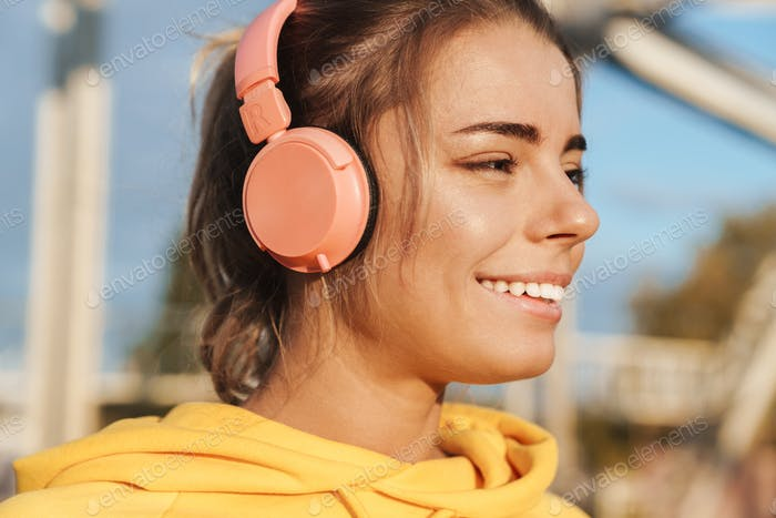 Optimistic pretty young fitness woman with headphones.