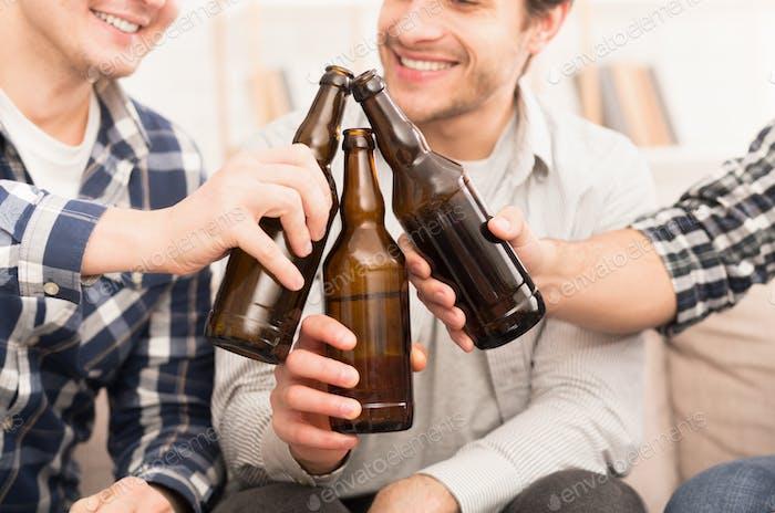 Prost. Freunde klingeln Bierflaschen zu Hause
