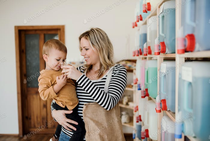 A young woman with a toddler boy buying liquids in zero waste shop.