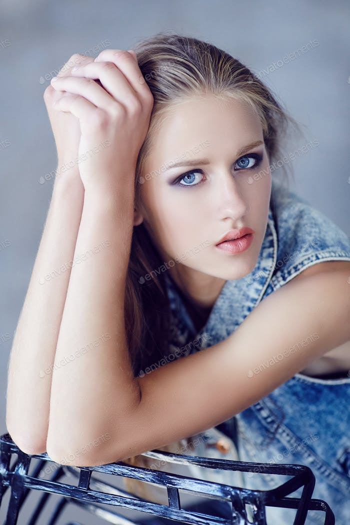 A girl with blue eyes and in jeans jacket.