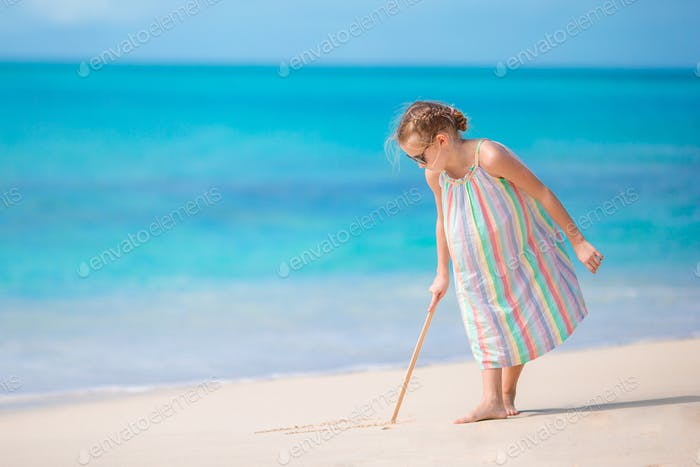 Adorable little girl at beach during summer vacation drawing on sand