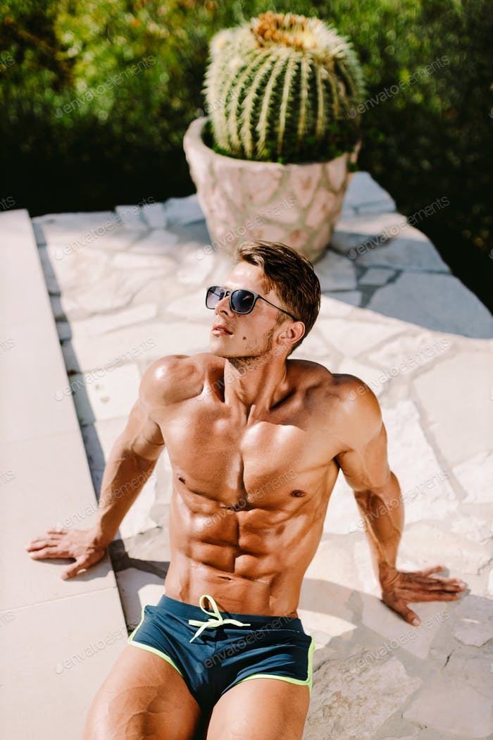 Sexy muscular man in swim trunks relax and posing near swimming pool outdoors