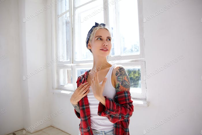 Positive young attractive blonde woman with tattoos dressed in checkered shirt