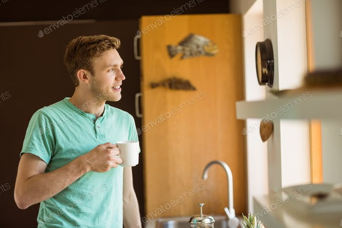 Young man smiling and holding coffee at home in the kitchen
