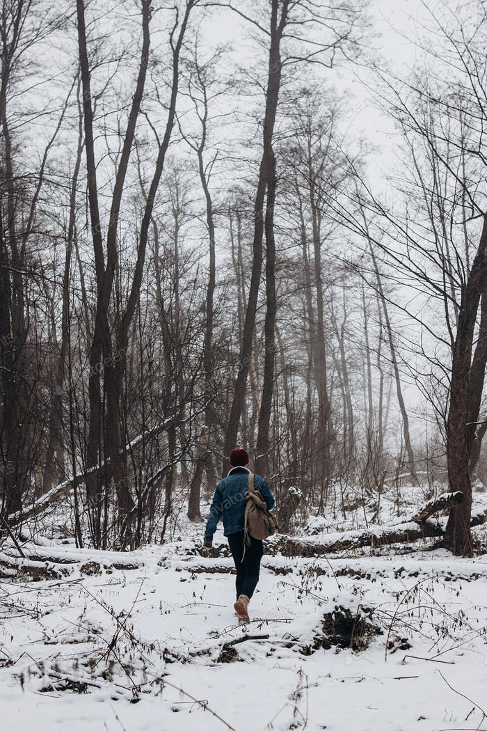 Stylish hipster traveler with backpack in red hat walking in winter snowy forest