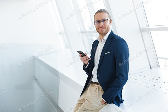 Pleased young businessman indoors in office