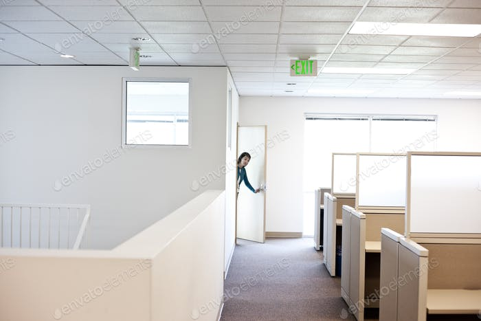 Office worker coming into cubicle work area of new office.