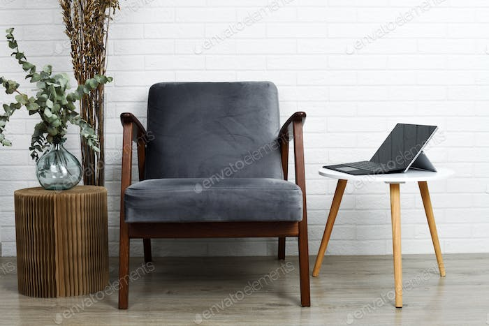 Grey armchair and small table with tablet