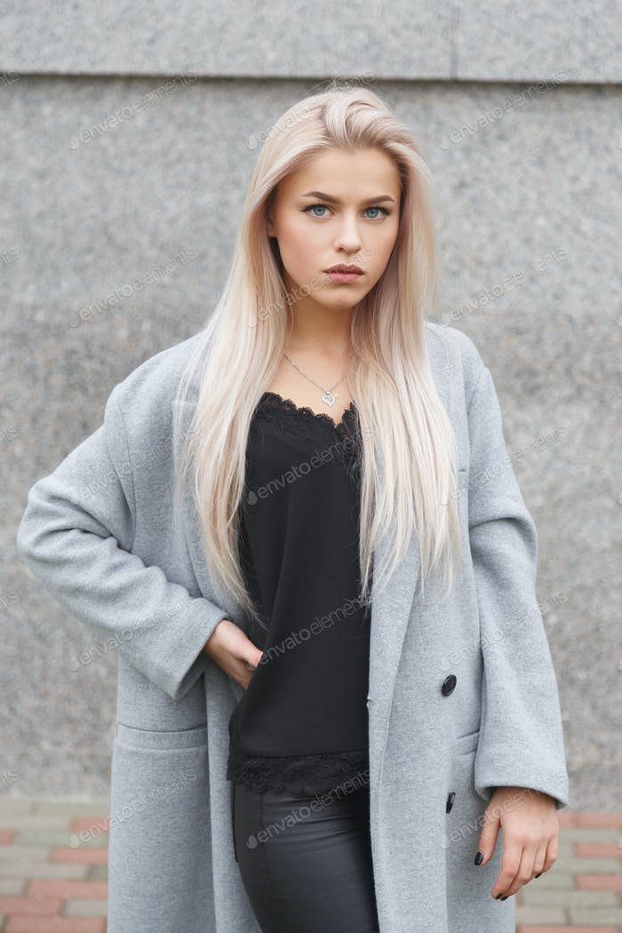 Portrait of a beautiful young blond woman in grey coat and black leather pants. Street fashion look