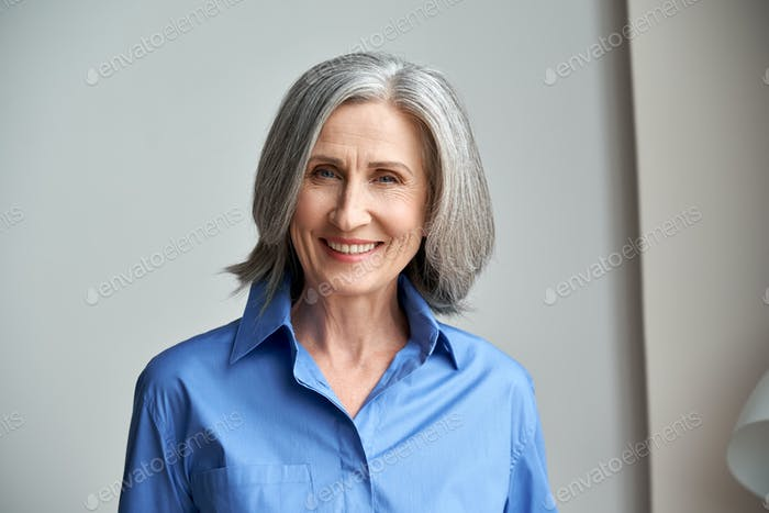 Smiling sophisticated mature grey-haired woman headshot portrait.
