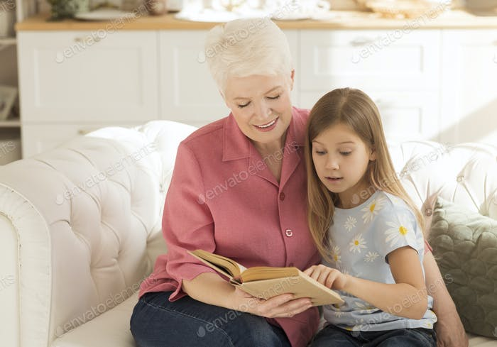 Elderly lady and her granddaughter with interesting book on sofa at home