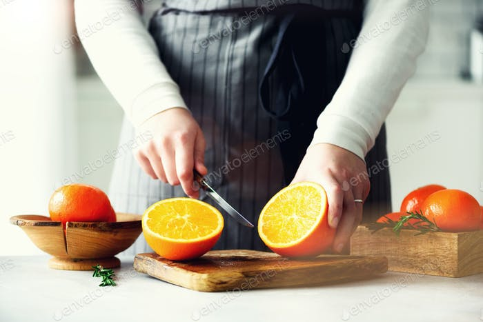 Woman hands slicing orange, cutting citrus fruit. Knife, wooden cutting board on design white
