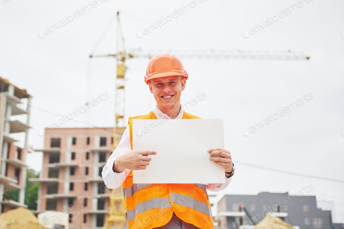 architecture and home renovation concept - man in helmet and gloves with blueprint in factory