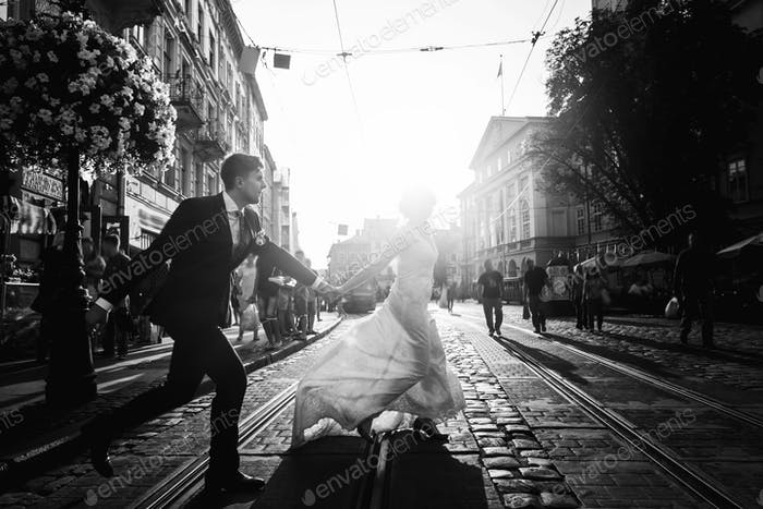 Romantic, fun newlywed couple running across paving road in city street at sunset