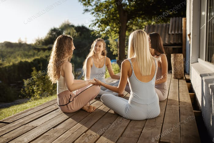 Four young girls are sitting in the lotus position in a circle on a wooden podium in the garden near