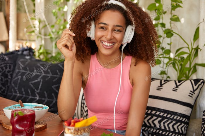 Happy Afro American female meloman listens music with high volume in headphones, sits in cafeteria,